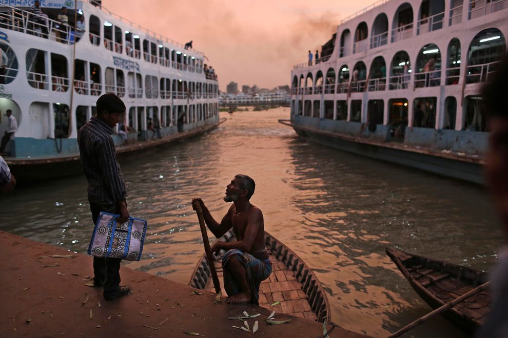 A boatman negotiates with a potential customer at the Sadarghat Terminal on the Buriganga River in Dhaka, Bangladesh, on Sept. 7. (Kevin Frayer/Associated Press) #