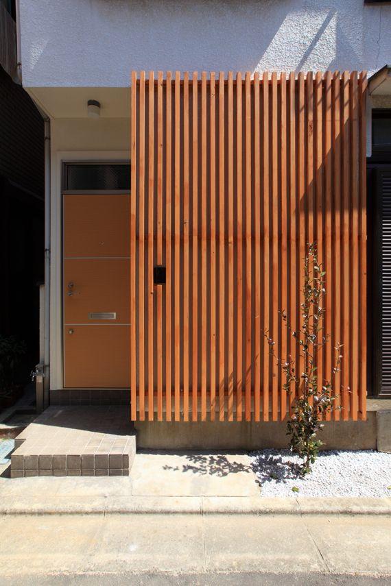 木製ルーバーとシステムキッチンが決め手に 玄関 格子 玄関