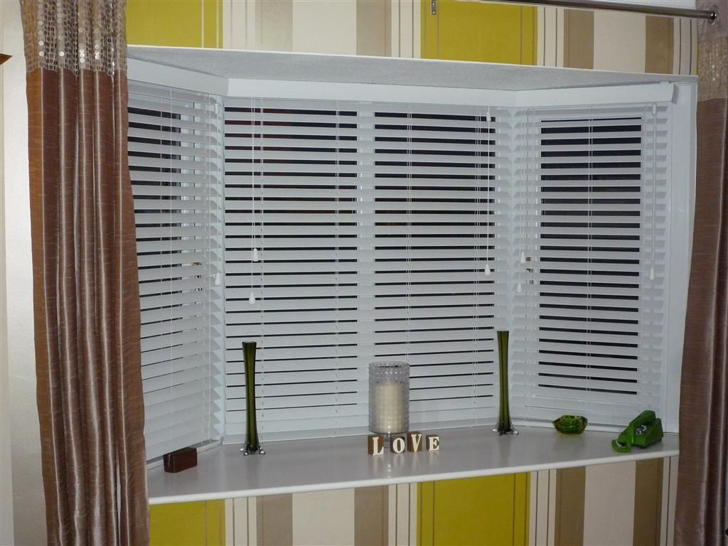 White venetian blinds covering bay windows revealed behind for Window cover for home