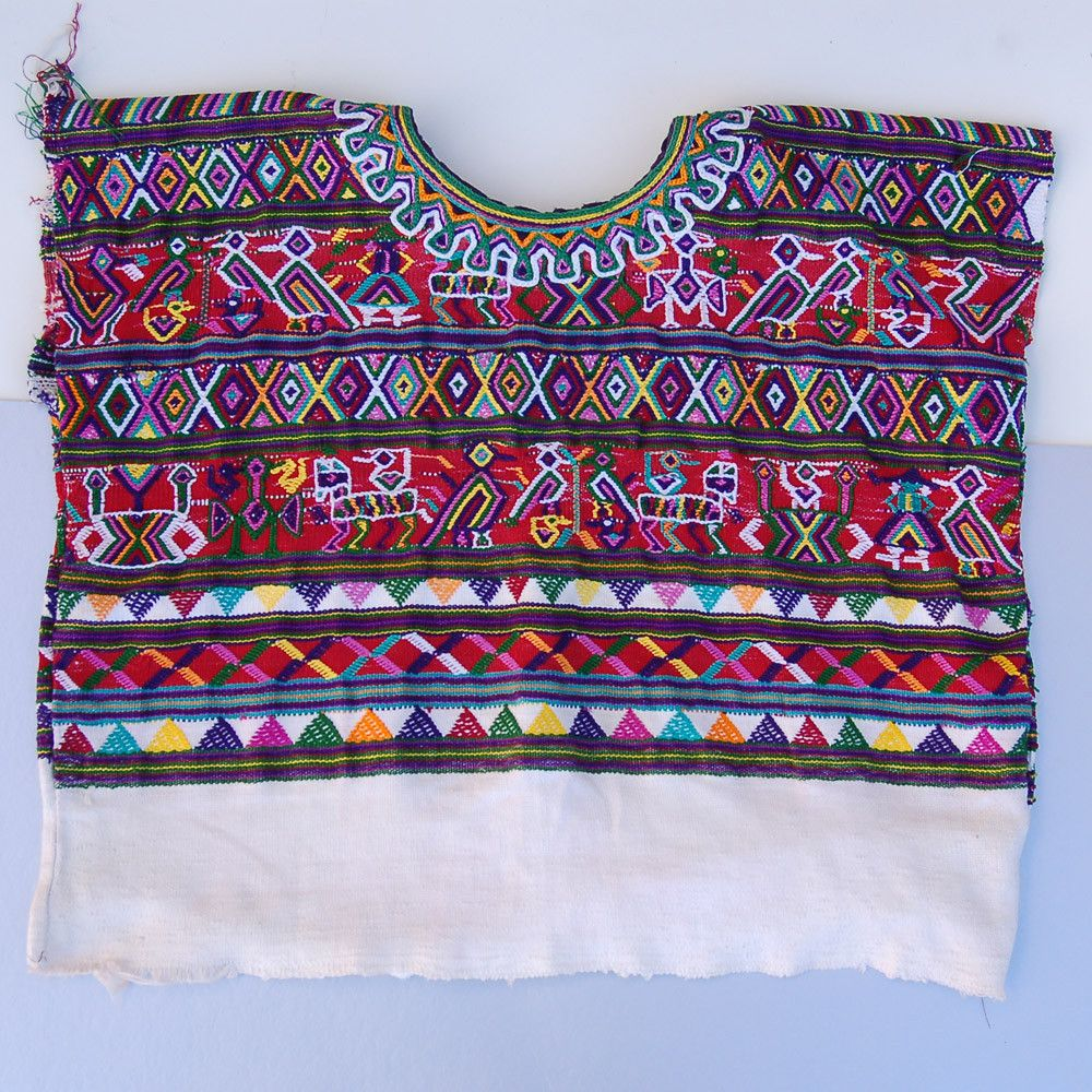 Mayan blouses or huipils are hand woven on a back strap loom. This one is from the highland village of Nebaj. The color and pattern of huipils are specific to each individual village. Imagine getting up in the morning and putting on exactly what every other women and girl in your community wears. Mayans believe that it is their duty to dress beautifully to compliment the fantastic nature that surrounds them. This piece should be considered art wear.