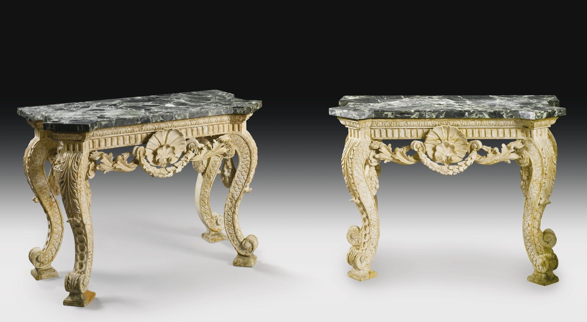 A pair of white-painted pine marble top pier tables in the manner of William Kent The present pair of tables shares a number of affinities to the strong Palladian designs of William Kent, especially to tables which he most probably designed for Houghton Hall circa 1730 including a table centered by a shell flanked by floral garlands with similar acanthus-carved S-scrolled legs which have scaled sides