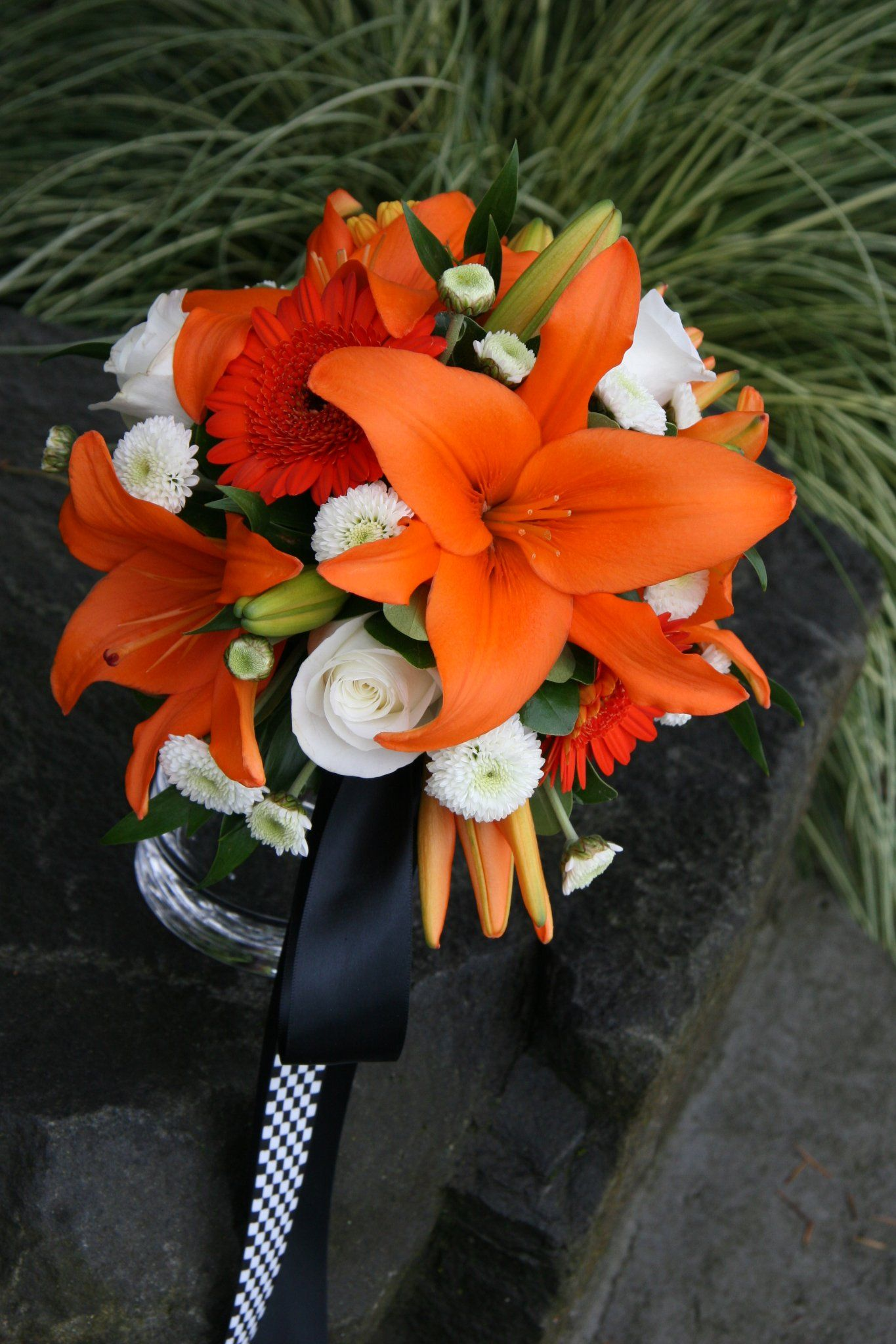Striking wedding bouquet which features orange lilies buds striking wedding bouquet which features orange lilies buds orange gerbera daisies white roses white mums greeneryfoliage hand tied with blackblack izmirmasajfo