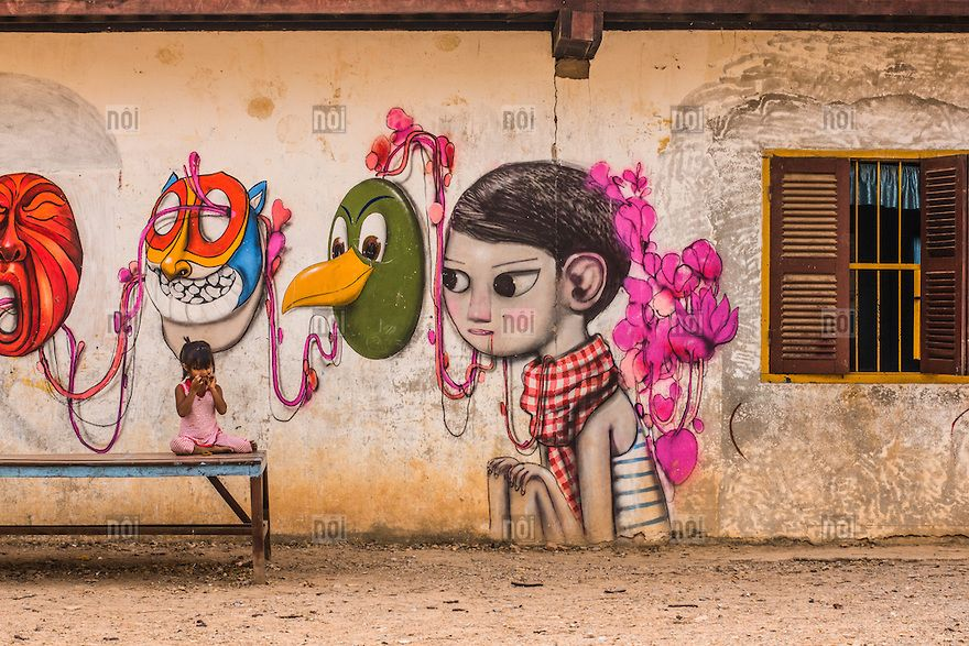 [photo by Jérémie Lusseau] A little Cambodian girl sits on a bench in front of a graffitied wall in Battambang, Cambodia