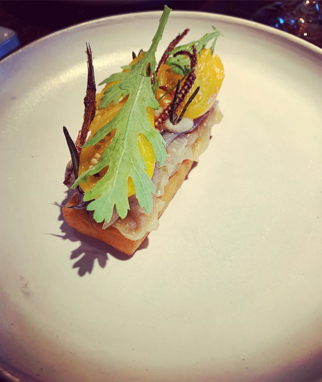 Cured anchovies and its crispy spines on panisse, cream of roasted eggplant, salted plums, olive herb and a jus of fermented tomato, tomato water seasoned with tomato vine vinegar and split with bay leaf oil