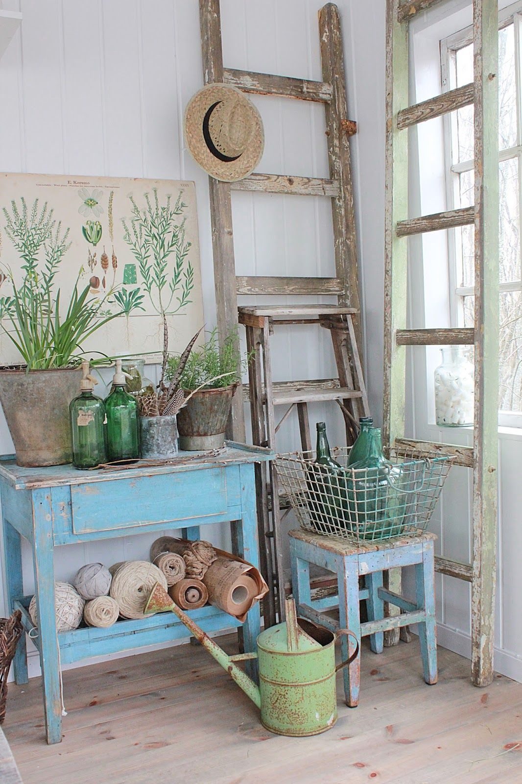 Rustic corner with ladders, painted stool, table, watering can, basket, pots and bottles in a potting shed.
