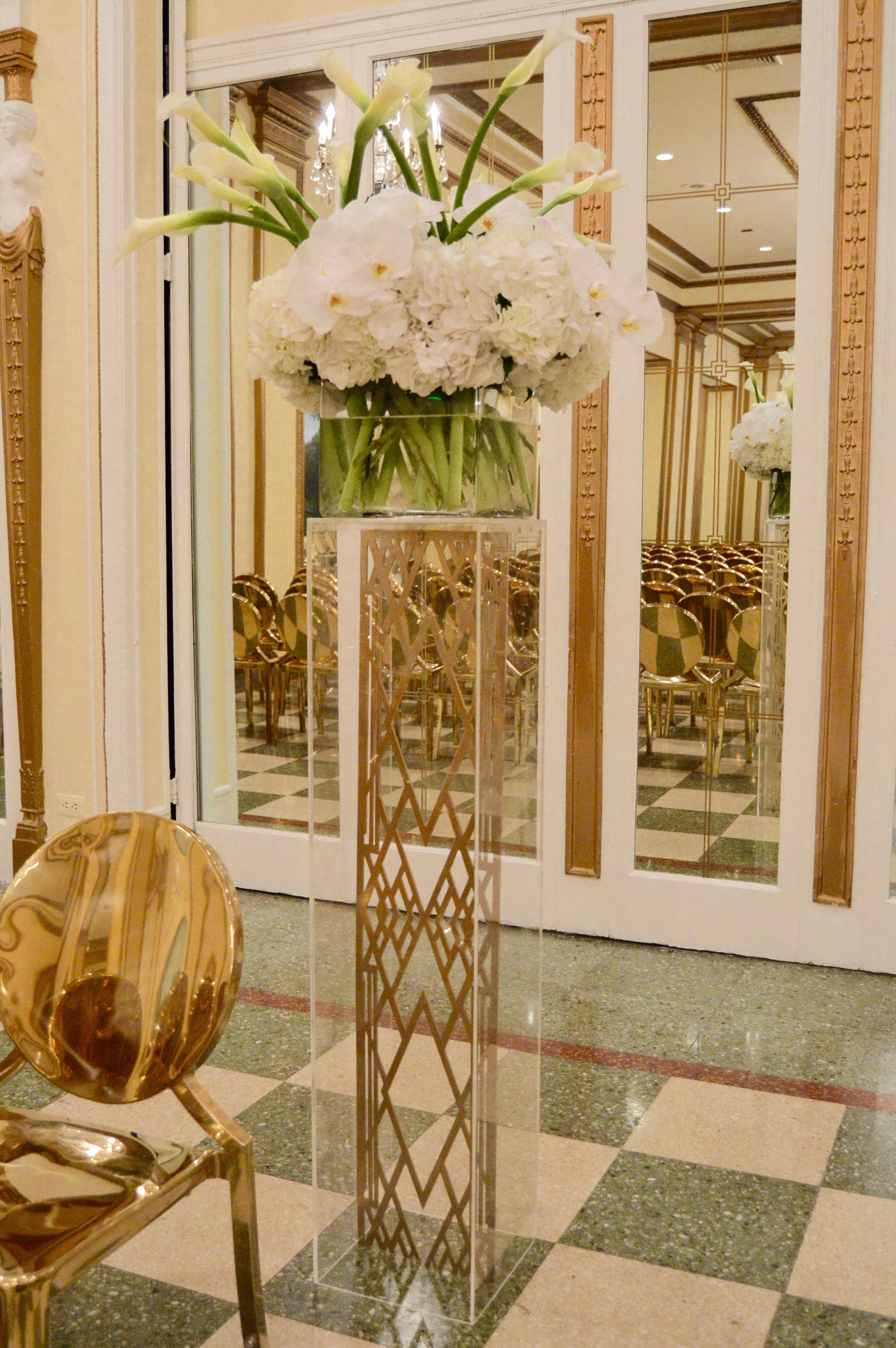 Custom art deco details within an acrylic column, florals of mounded white hydrangea, calla lilies and phalenopsis orchids. Let us customize your event!