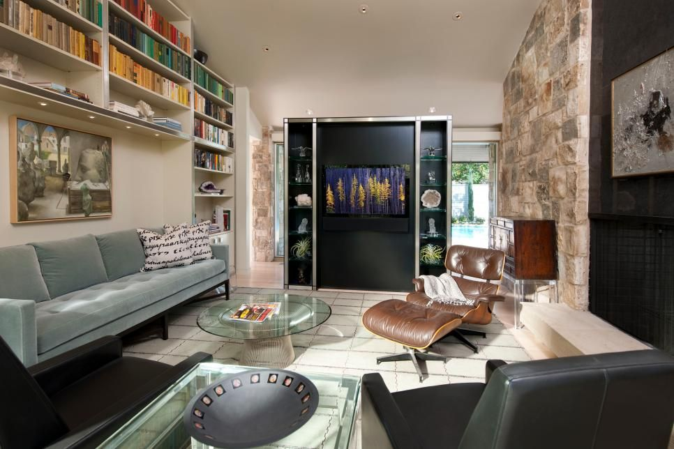 Classic furnishings and great art contrast with vintage stone and sleek finishes for vibrant den with lots of texture.