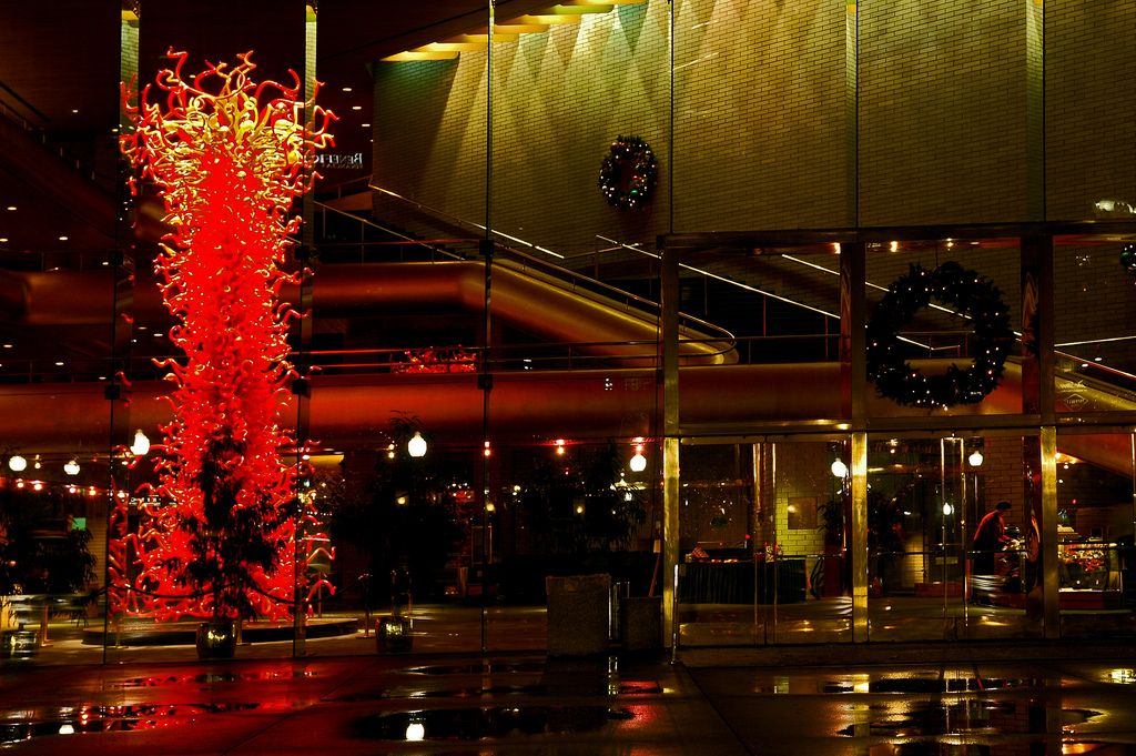 Abravanel Hall (1)-Abravanel Hall is the home of the Utah Symphony Orchestra, Salt Lake City, Utah, USA. This photograph looks in through the entryway windows and doors. The organge-red glass sculpture is by Dale Chihuly.