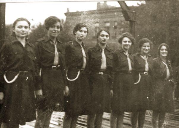 """קבוצת בית""""ריות, סין. שבע נשים ניצבות בשורה על גשר לבושות מדי התנועה."""
