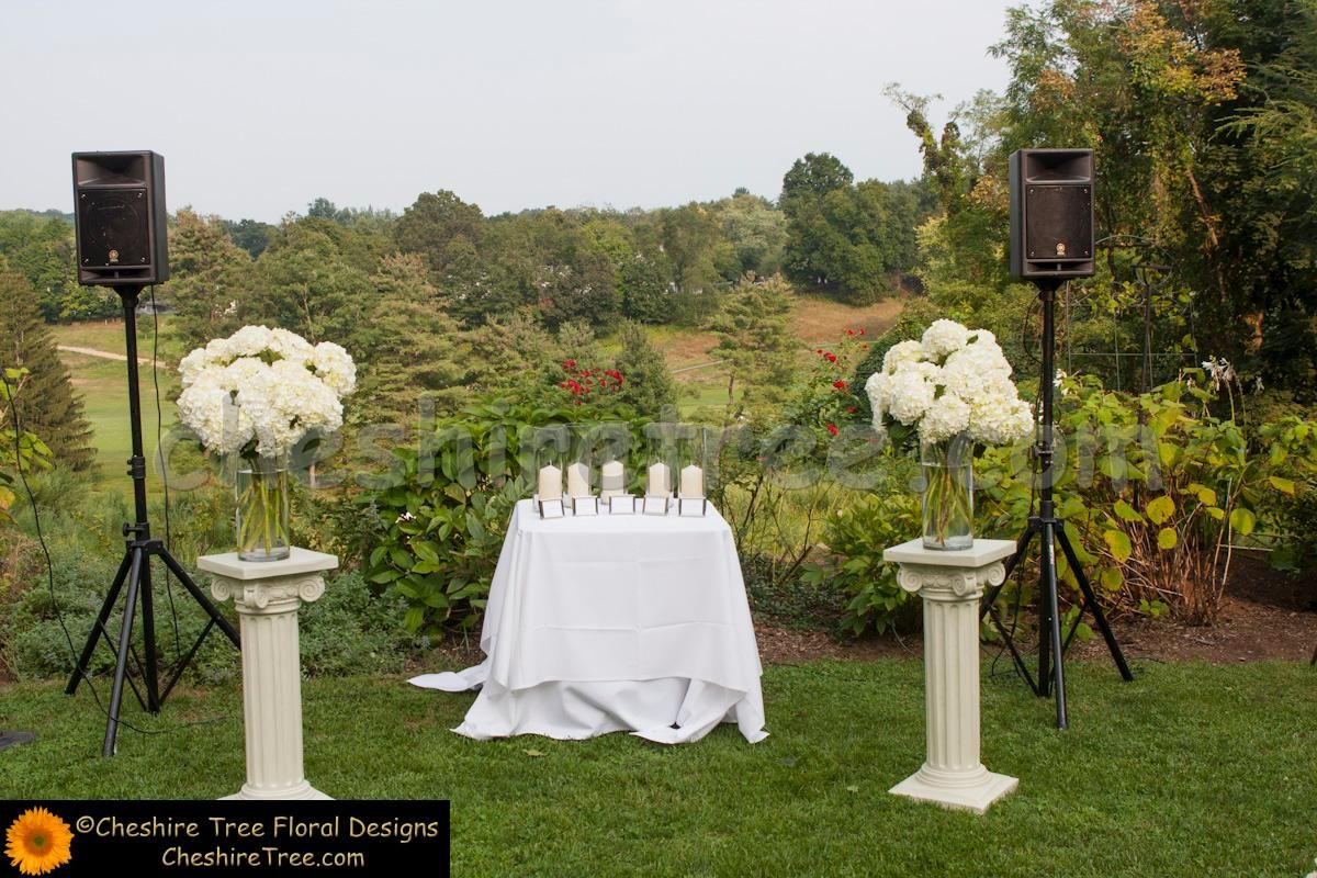 The ceremony area flanked by arrangements of white hydrangea atop ...