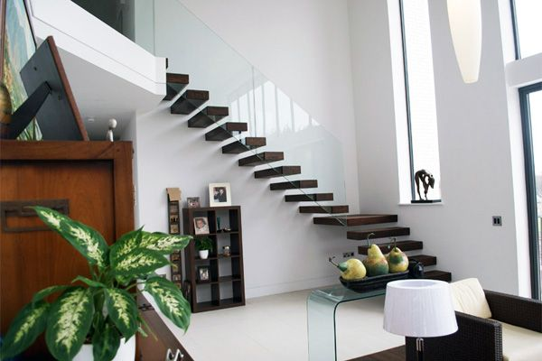Black wood floating stairs definitely give off a ...
