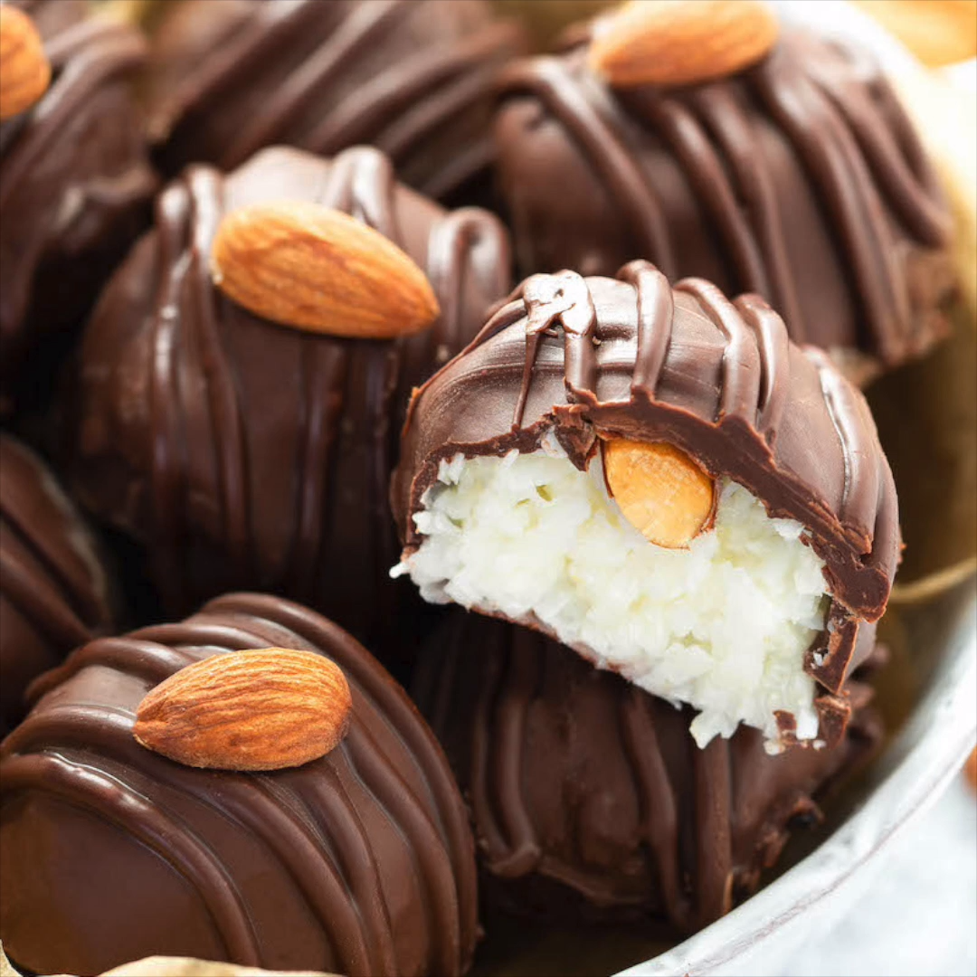 These Almond Joy Truffles only need four ingredients and taste even better than the candy bar! These truffles have a creamy coconut center with a hidden Fisher Nuts Almond and a dark chocolate coating! #ThinkFisher #ad