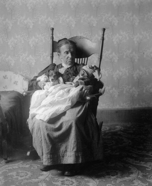 Clara Middleton: Woman with Pets. Madison, Wisconsin, ca. 1909. Source: Wisconsin Historical Society. An unidentified woman sits in a rocking chair holding the Middleton family dog, Tootsie, and a cat. The pets are dressed in gowns and the cat wears a sweater and knit hat.