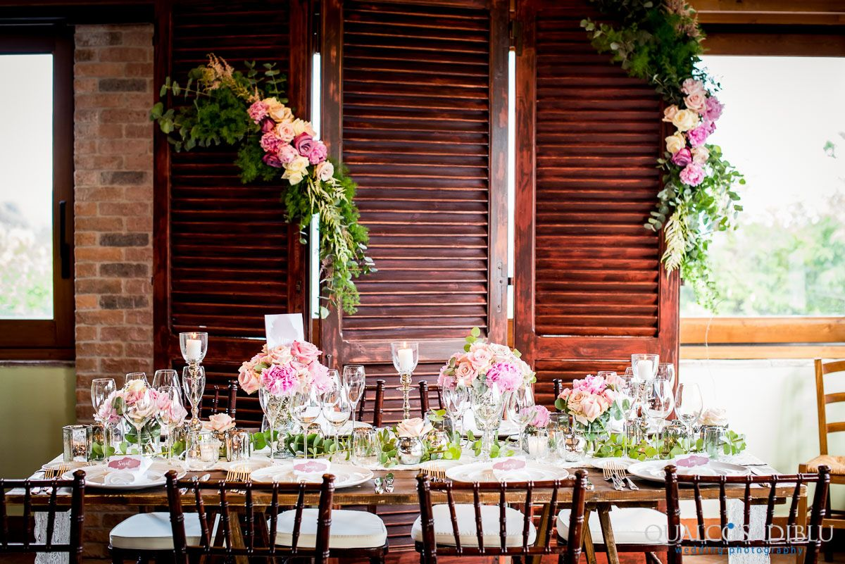 Vintage shutters used as a classic back drop for a head table- romantic pink roses shading to ivory with eucalyptus.