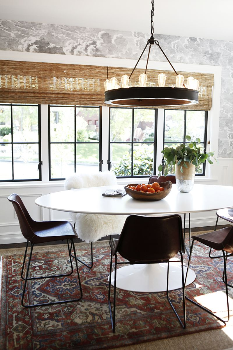 A modern dining space with industrial chandelier and dark clouds on the wallpapered accent wall