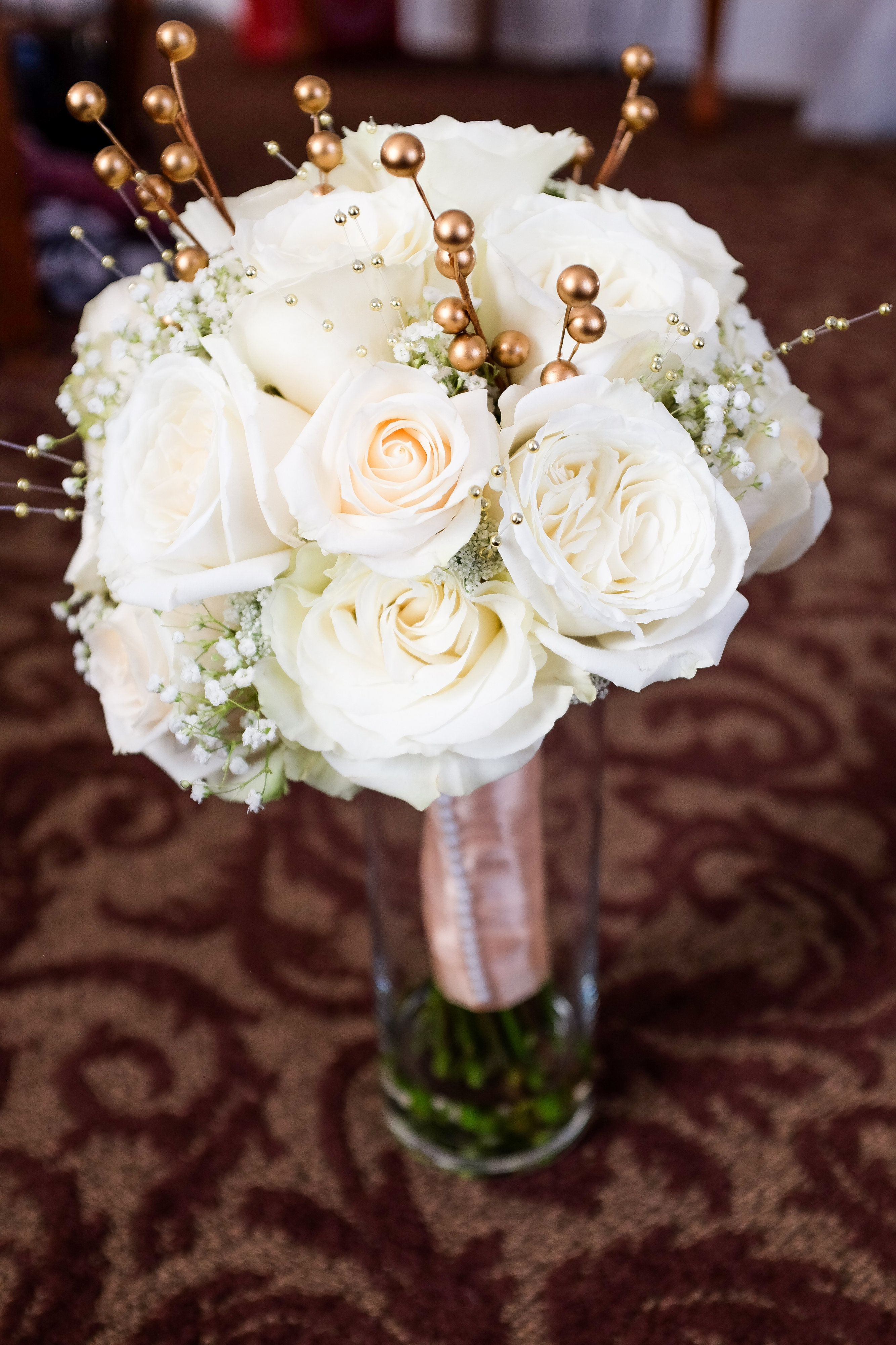 A Beautiful Wintery White Wedding This Bouquet Was Composed Of Mondial Roses Baby S Breath And Gold Berries Phot Winter Bouquet Bridal Bouquet Babys Breath