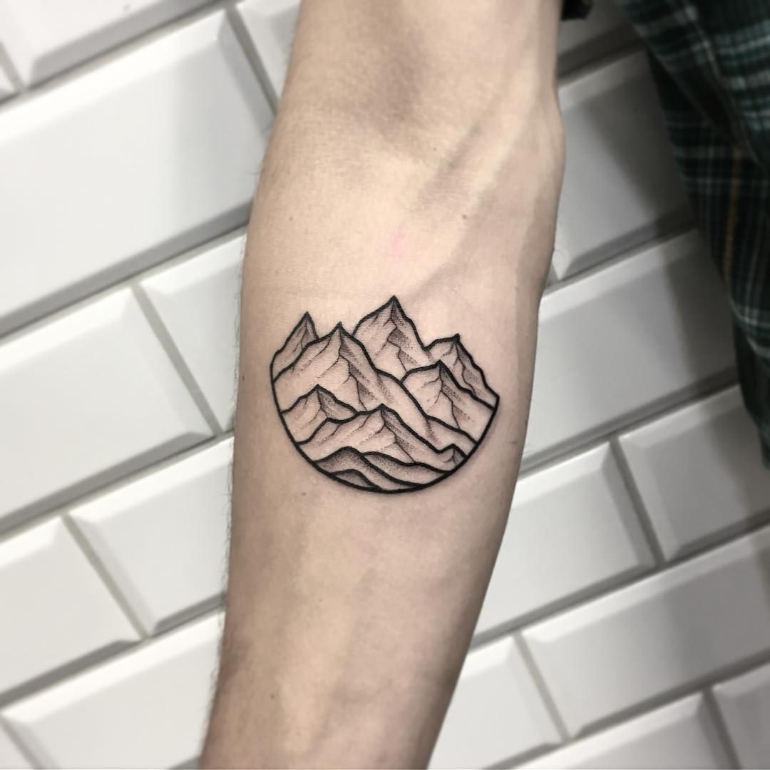 A minimalist mountains landscape tattoo on the right