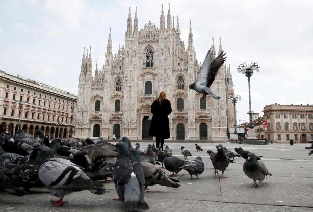 A woman stands in front of the Duomo gothic cathedral, in