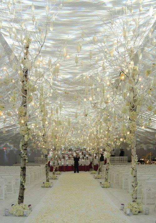 Une décoration de mariage en blanc avec des arbres et des bougies suspendues