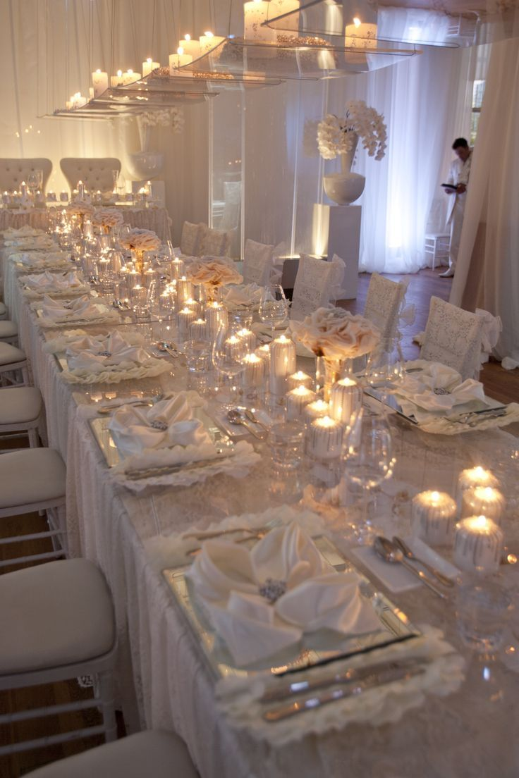 Head table filled with flowers candles lace linens and for Glass tables for wedding reception