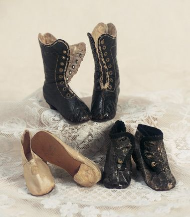 "Three Pairs of French Doll Shoes Signed Huret    Suitable for classic Huret poupee,16""–17"" (40–43 cm). Includes black kidskin boots with wooden heels,eight pairs of brass lacing grommets (no laces); ivory silk ball slippers with silk covered wooden heels; and brown ankle boots with wooden heels and three gold buttons on each. Each with border-outlined soft kidskin soles stamped Huret A Paris. Good condition. Circa 1860."