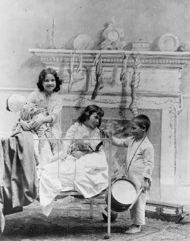 1896 two little girls in bed playing with japanese dolls a little boy with a drum stands at the bedside stockings hang from the mantel b - Vintage Christmas Photos
