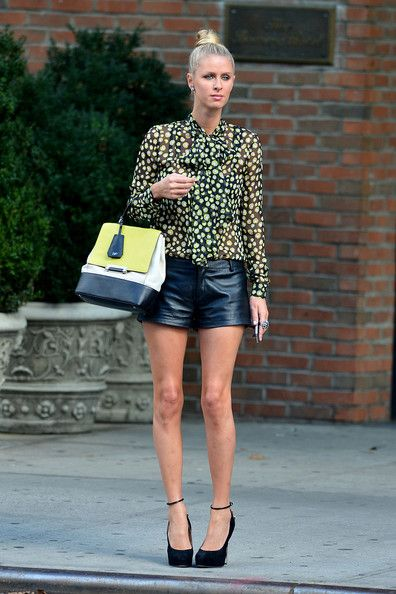 Nicky Hilton wears short leather shorts, a colorful sheer top and black heels #streetstyle #fashion