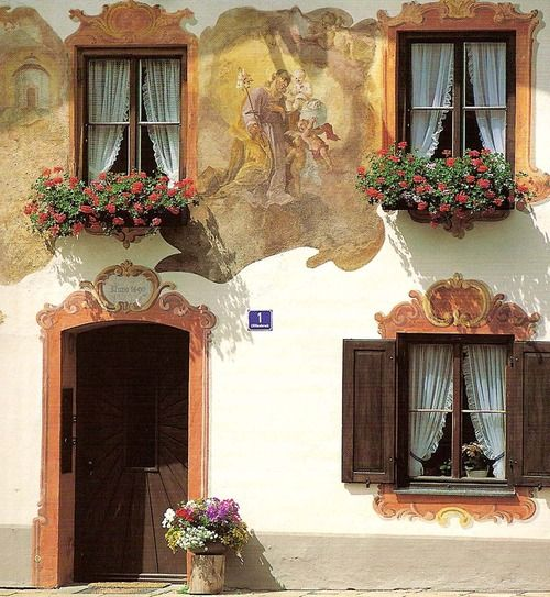 scrolls painted to frame windows with windowboxes and a door ... adds an elegant touch