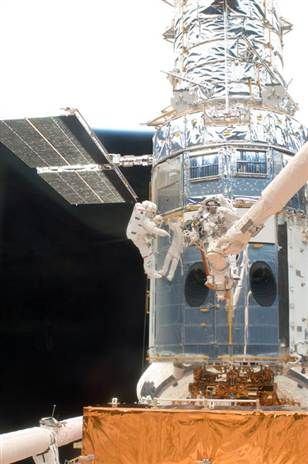 Hubble Telescope May Operate Until 2018   David Reneke   Space and Astronomy News   What appears to be a number of astronauts, because of the shiny mirror-like surface of Hubble, is actually only two — John Grunsfeld (left) and Andew Feustel during a  2009 spacewalk.