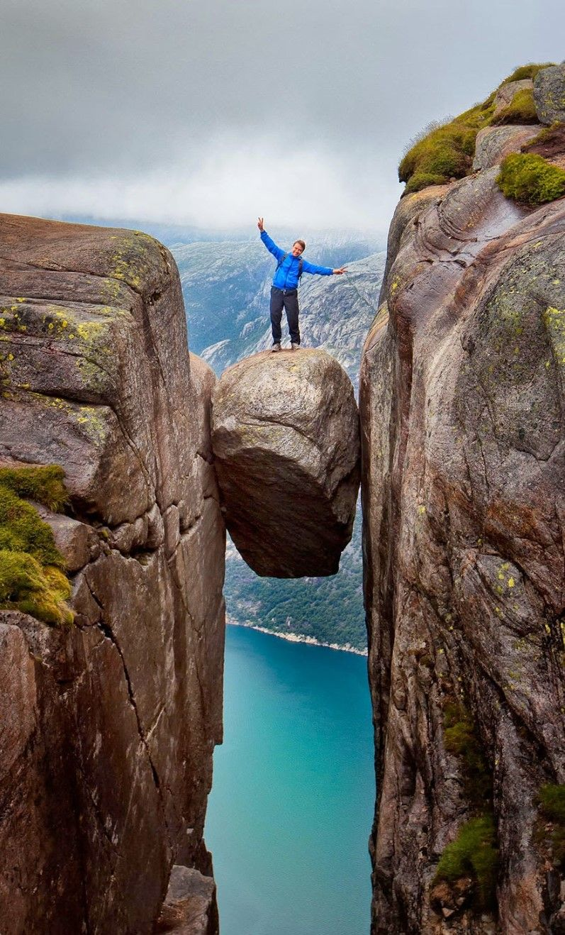 Kjeragbolten, Rogaland, Norway  A man daringly stands atop Kjeragbolten, a boulder wedged in a mountain crevice that's suspended above a 3,228-foot deep abyss.