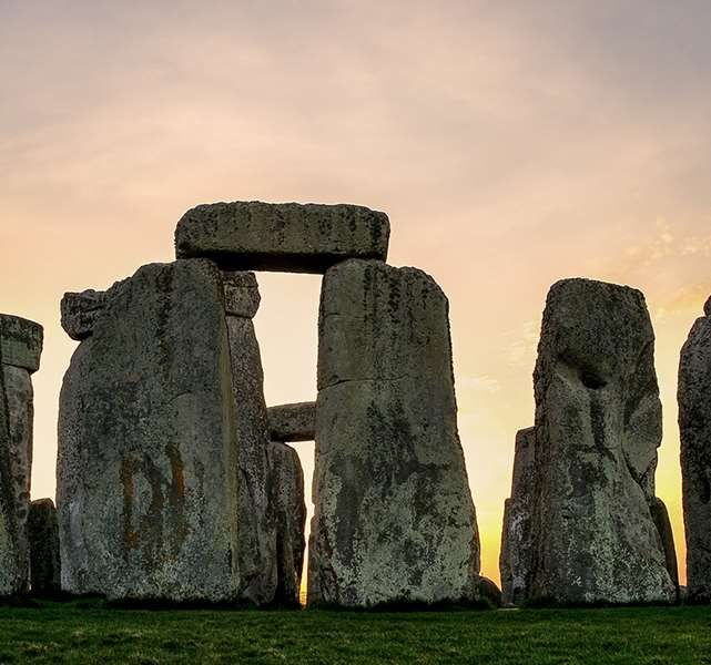 The hard, textured megaliths of Stonehenge stand in stark contrast to the soft pink and yellow skies of sunset
