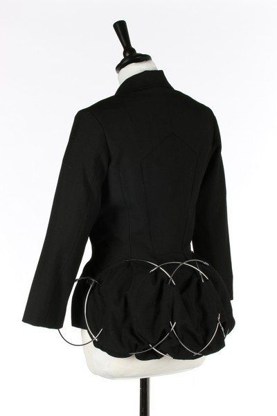 * Junya Watanabe/Commes des Garçons transformation jacket/handbag, Autumn-Winter, 1999. labelled and size M, of black wool with front button closure, the hem of the jacket inset with six metal rings which create a bustle-effect and also form handles when the jacket is folded to create the handbag