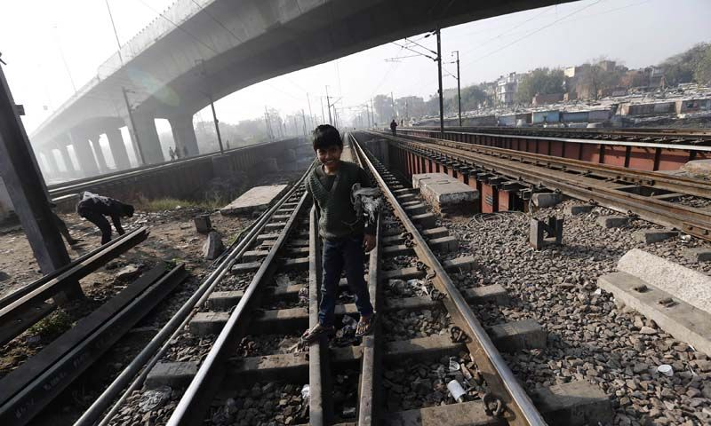 A ragpicker boy smiles as he stands on the tracks at a railway station in New Delhi.— Photo by Reuters
