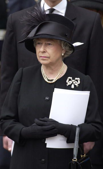 The Queen attending Queen Elizabeth, The Queen Mother`s funeral at Westminister Abbey on 9th April 2002. She is wearing the Kensington Bow brooch.