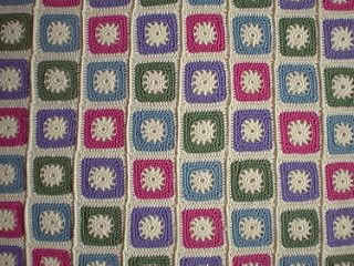 The cream cogs at the centre of these crochet blocks are surrounded by coloured squares and finished off with a cream border. The blocks are then crocheted together and a simple edging added to complete this blanket.