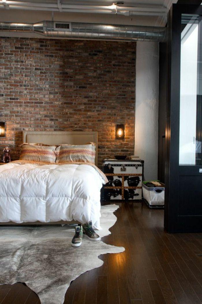 une jolie suite parentale tapis en peau d animal parquette en bois fonce mur de briques rouges