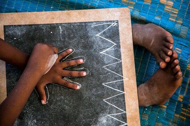 A child in a nursery Zanzibar draws his hand on a blackboard.  Location: Zanzibar, Tanzania