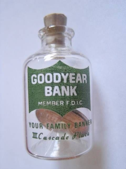 1968 PENNY IN A MINIATURE GLASS BOTTLE ADVERTISING GOODYEAR