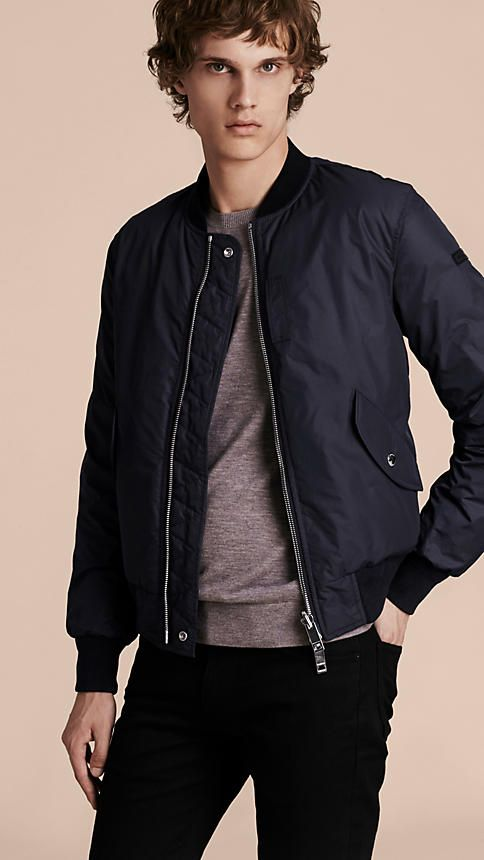 A reversible neat fit bomber jacket quilted and filled with insulating down. The modern design features ribbed cuffs and light padding to fend off the cold.