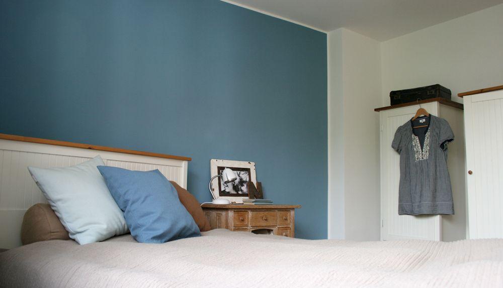 Weisses Bett und Kleiderschränke vor blauer Wand