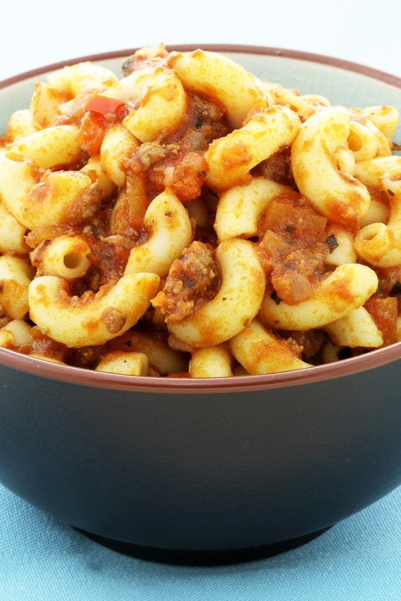 Recipe including course(s): Entrée; and ingredients: beef broth, black pepper, cheddar cheese, dark brown sugar, dill pickle, elbow macaroni, extra-virgin olive oil, garlic, ground beef, kosher salt, onion, red bell pepper, red wine vinegar, tomato sauce, Worcestershire sauce