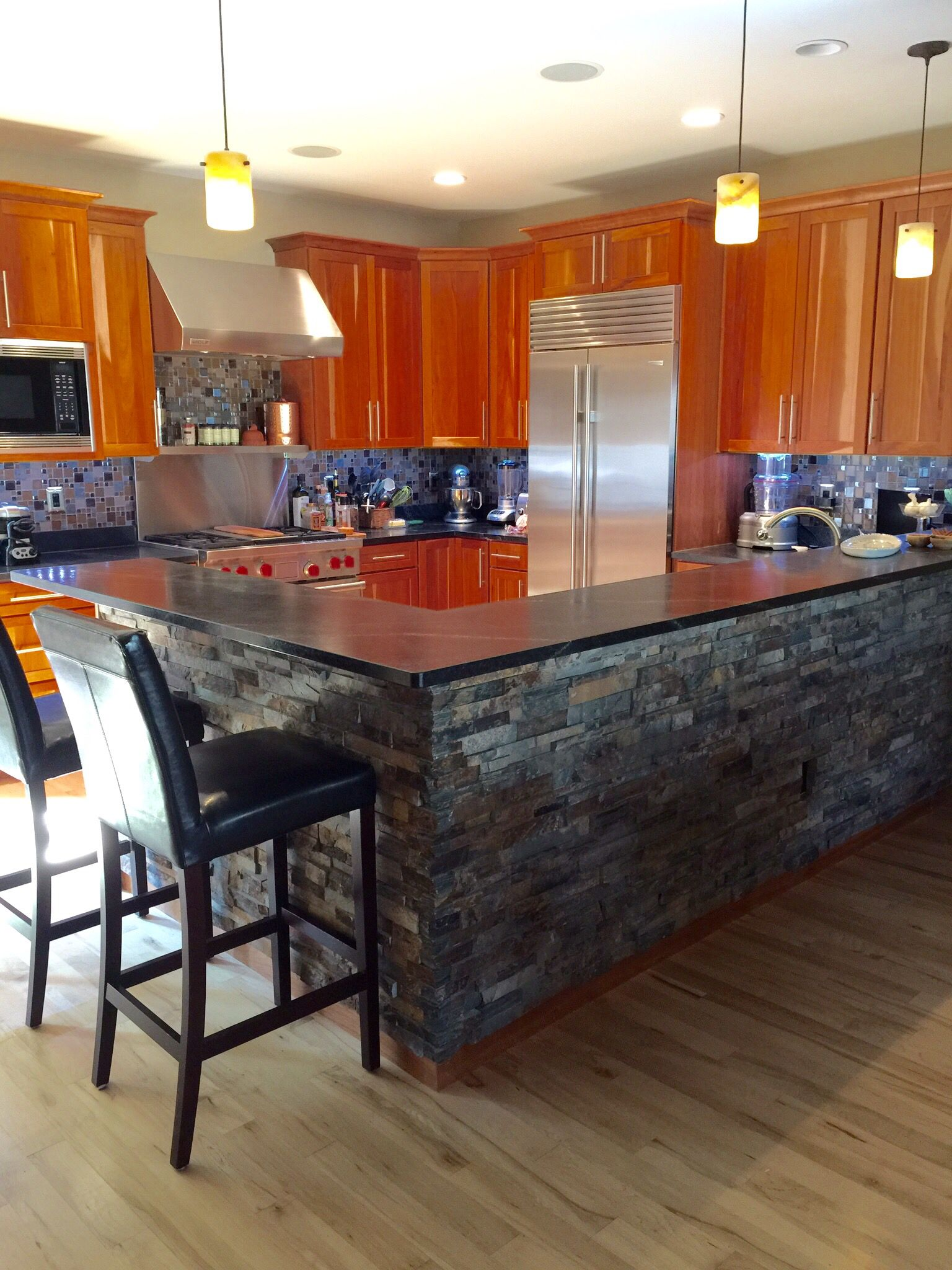 Awesome gourmet kitchen with dry stacked stone bar front and glass ...