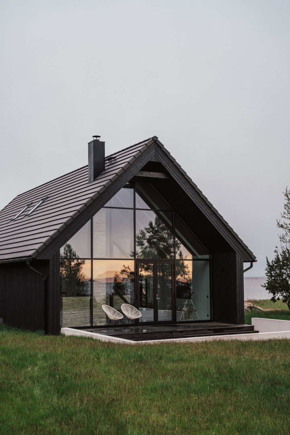 Summer house on an Estonian beach formed of two black gabled volumes