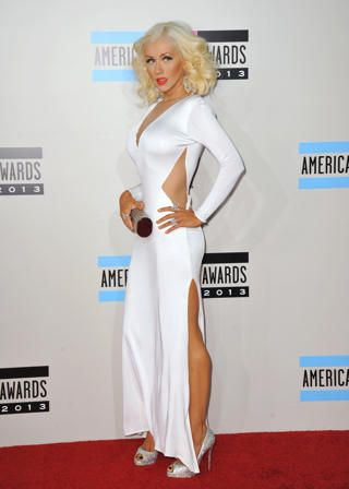 """Christina Aguilera -- Christina Aguilera was a vision in a low-cut, white column Maria Lucia Hohan gown featuring cutouts at the waist — which accentuated her tiny physique — as she arrived at the 2013 American Music Awards in Los Angeles on Sunday. The """"Voice"""" star completed her glam look with blinged out accessories and retro hair and makeup. Credit: Jason Merritt/Getty Images"""
