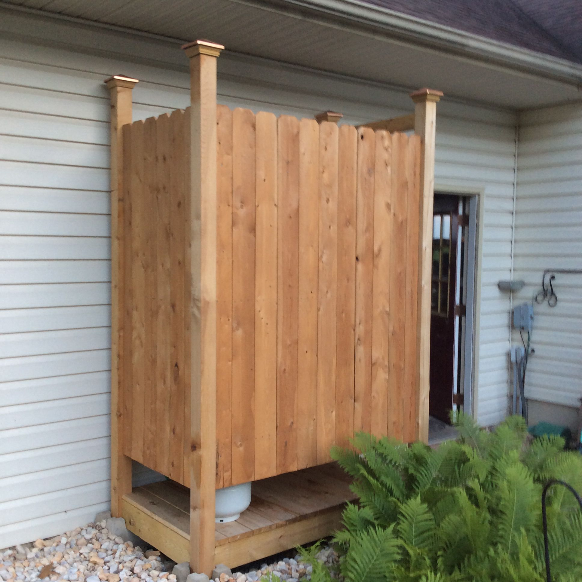 Outdoor shower hubby made from cedar fencing and a camping shower kit hooks up