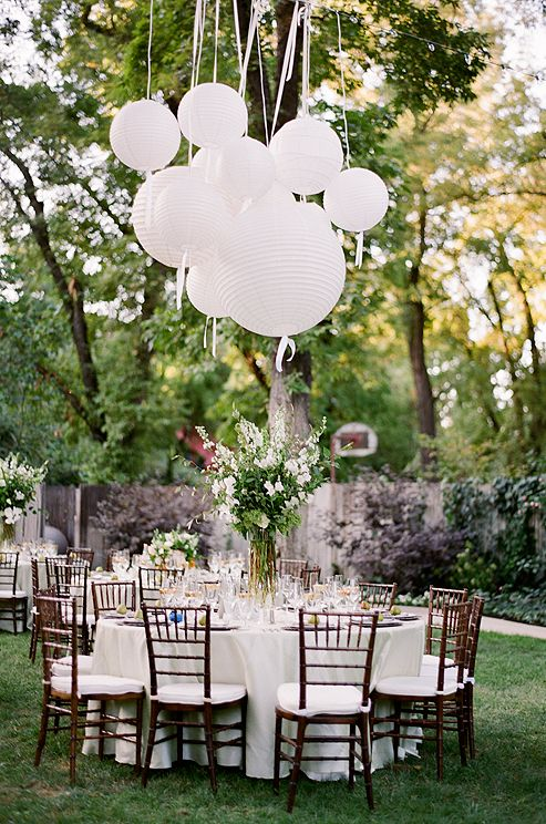 Tables set with grey linens were scattered around the bride's parents backyard.