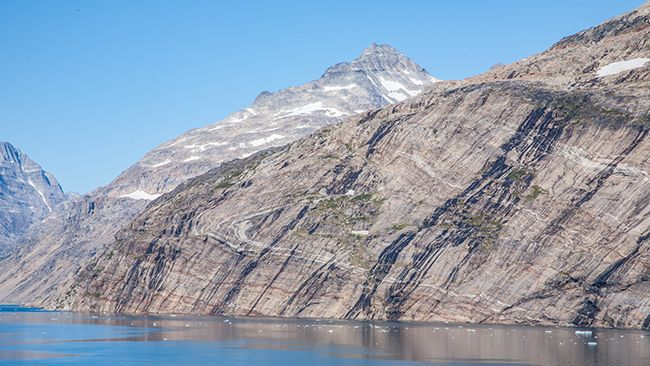 "This is at Prins Christian Sund (""Sound""), South Greenland. The rocks are likely Palaeoproterozoic supracrustals – rocks that formed original as stratified rocks on Earth's surface (sediments, volcanics) before being dunked down into Earth's crustal interior and subjected to intense metamorphism and ductile deformation. Now, billions of years later, here they are back at the surface again."