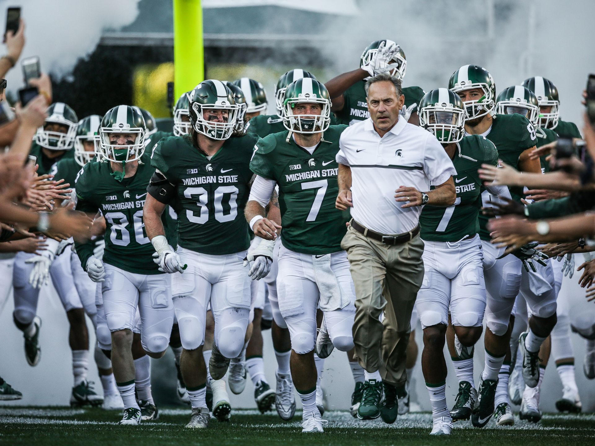 The Michigan State Spartans Team Runs Out Of The Tunnel Led By Head Coach Mark Dantonio Before Their Season Op Michigan State Michigan Michigan State Spartans