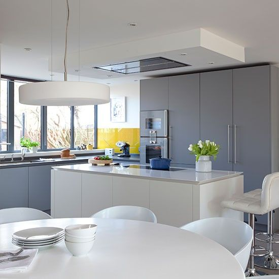 This sleek grey kitchen is livened up with a mustard for Yellow and gray kitchen