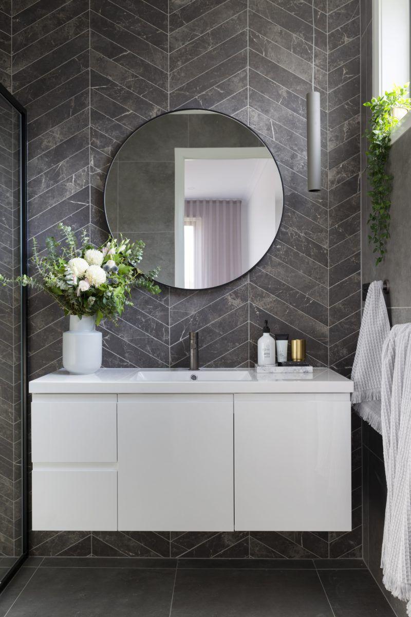 Photo of Ein modernes Bad mit Chevron-Fliesen in Marmoroptik und Fußböden in Betonoptik. Runden…
